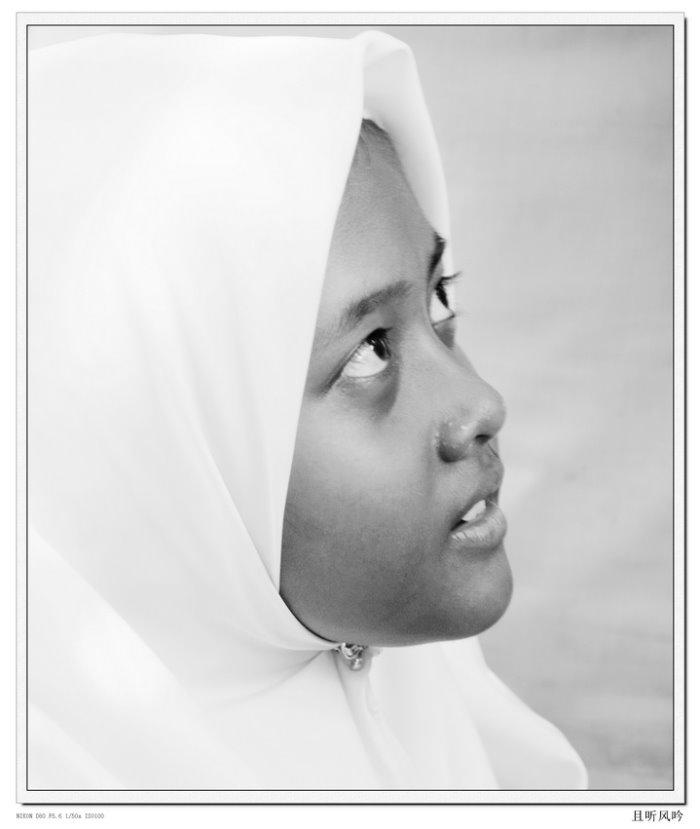 """遮不住的美丽 摄影:杨煌达 (厦门) 高中83届 日前到大马旅游,所到之处都可以看到戴着盖头的穆斯林女性,她们神秘的面纱令我好奇,于是我把镜头的焦点从风景中转移到的人物,在街头抓拍了不少,从神秘中看到了美丽与大方,还有青涩与纯真,传统中不泛时尚……抓拍时被发现了,我担心被责难。没有语言的交流,只是简单的一个动作表示""""可以吗?"""",换来的是落落大方的首肯,她们用微笑表达了善意,给了我意外的惊喜。"""